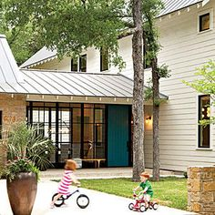 """Tim calls the project a """"cartoon"""" of the farmhouse style, updated with many youthful and graphic details. Black hinges and bold window mullions (made of painted mahogany, not metal) dial up the impact, as does the home's most eye-popping accent, the bright blue front door (painted Naples Blue"""