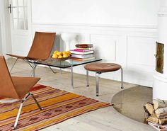 Fresh fruit, white stained wooden floor, Poul Kjærholm PK22 chairs, PK33 stool and PK61 glass table.