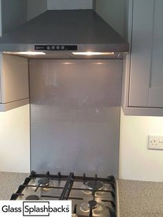 Grey glass cooker splashback in simple kitchen. Did you know that we stock standard sized glass splashbacks, which can be dispatched in 24/48 hrs in a colour of your choice? Visit www.glasssplashbacks.com for more inspiration!