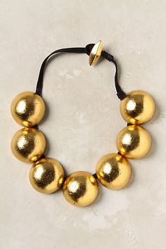 Aurous Tune Necklace   spray paint large beads gold and string onto some lace.