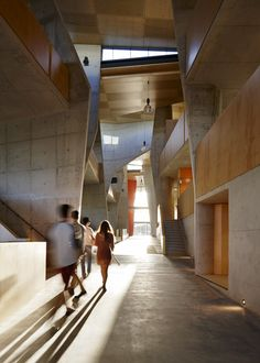 Curving concrete walls frame secluded meeting rooms along the central thoroughfare of this architecture faculty building.