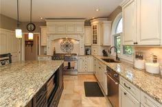 Traditional Kitchen with Undermount sink, Kitchen island, Pendant Light, limestone tile floors, Subway Tile, Glass panel