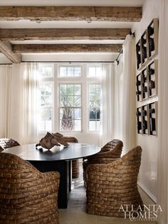In the adjacent dining area, raffia chairs purchased at High Point Market sidle up to a Julian Chichester tabletop with a custom base. Turner also commissioned the mounted wood-block artwork from Soicher Marin.