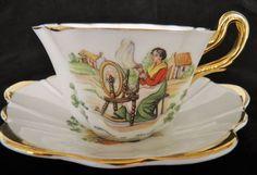 Šálek na čaj * bílý zlatem zdobený porcelán s malovaným obrázkem ženy s kolovrátkem.