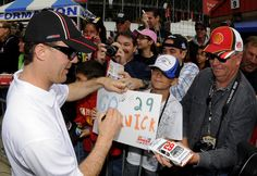 Kevin Harvick stops to sign autographs after being inducted into the Auto Club Speedway Walk of Fame for his 2011 Auto Club 400 win.