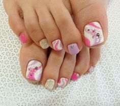 A very cute and fun looking toenail art design. A series of matte white, pink and silver glitter polishes are used as base colors for the nails. On top of the white base, swirling shapes in pink and periwinkle polishes are painted with a dash of silver glitter and violet beads.