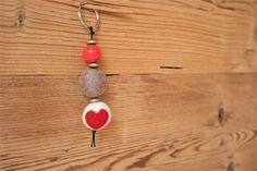 Schlüsselanhänger mit zwei Filzperlen in beige und weiß-rot mit Herz, drei goldfarbenen Holzlinsen und einer roten Holzperle. Der Schlüsselring ist silberfarben. Aufgefädelt auf eine schwarze Kordel. Dieser Schlüsselanhänger hat eine Länge von ca. 12 cm.