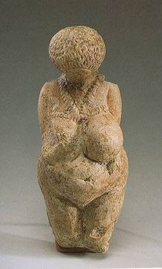 Female figurine, 23,000-21,000 B.C. Paleolithic. The faceless head bends towards the chest while the arms are pressed to the body with hands on the belly. Covering the surface of the head are rows of incisions indicating a hair style or cap. Relief work in the form of a tight plait convey a breast ornament tied up at the back. There are bracelets on the arms. The State Hermitage Museum