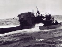 A small boat tied to a surfaced submarine which bobs on the water.