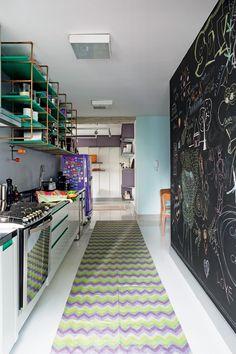 Esta cozinha colorida e moderna ficou ainda mais bacana com uma grande parede pintada com tinta para lousa. A ideia do escritório Superlimão Studio transformou o visual do ambiente, assim como a antiga geladeira que ganhou pintura em tom de roxo e a passadeira estampada.