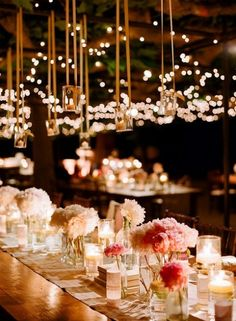 In this reception setting, the bride used inexpensive carnations for her floral and they were fabulously enrobed in candles.  The also used twinkle lights to add additional candy for the eyes. www.celebrationsbykat.com