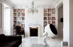 Classic architecture meets iconic furniture - french/ apartment/ white/ chandelier/ bookshelf/ living room/ fireplace/ light/ wood floors