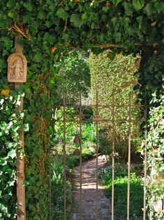 Iron garden gate and stone path into the secret garden