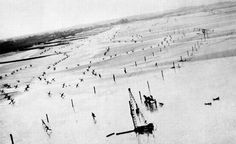 A low-flying Allied plane sends German soldiers running for shelter on a beach in France, before D-Day in 1944. The fliers were taking photos of German coastal barriers in preparation for the upcoming June 6 invasion.
