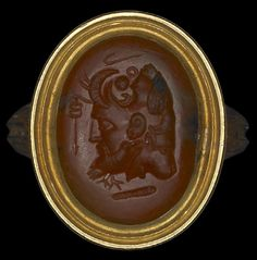 Red jasper gem engraved with a comic mask conjoined with a bearded face, a lion's head, a raven and an eagle; in the field are a shepherd's crook, caduceus and club of Herakles. Roman 1stC-3rdC