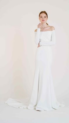 Meet Jenny Yoos Frankie gown for Fall 2020. Subtle enough for any venue, and stunning enough to make a statement, this sophisticated Knit Crepe gown hugs close to the body to make sure you are the main attraction. Featuring an off the shoulder neckline, knit crepe, a fit and flare silhouette, and a long gorgeous Chapel train skirt. This sleek & chic wedding dress is THE perfect Fall / Winter gown.