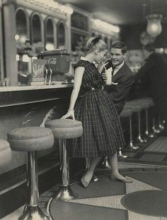 1950s couple in a date in a classic looking diner.: