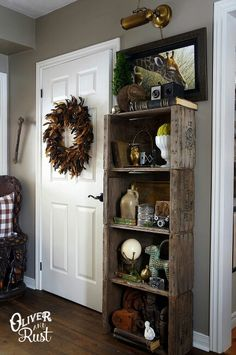 The feather wreath on the door combined with the brass lighting and weathered wood bookcase is absolute rustic perfection