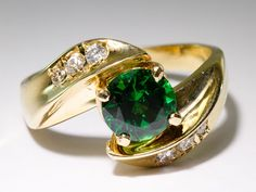 """Lot 234: 14k Gold, Chrome Diopside and Diamond Ring; Having a round cut green gemstone flanked by diamonds, 18CTtw, G-H, VS2-SI1; marked """"14k"""" inside band; includes a copy of an appraisal from Heritage Appraisals"""