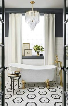 Black and white elegant and luxurious bathroom with crystal chandelier, clawfoot tub, and gold accents. Hexagon black and white tile flooring plays a starring role!