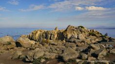 The rocky point with benches and trails at Lovers Point Park and Beach, Pacific Grove, CA