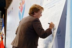 "President of Chile Michelle Bachelet signs the Call to Action, ""Women Leaders: Time to Step It Up for Gender Equality,"" during the closing ceremony of the high-level event on ""Women in power and decision-making: Building a different world,"" held in Santiago, Chile, on 27–28 February 2015. (Photo: UN Women/Carolina Sainz.)"