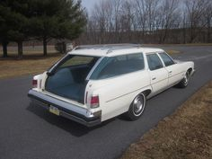 """A 1976 Pontiac Catalina Safari wagon, showing the """"clamshell"""" tailgate used by GM since 1971 in its lowered position."""