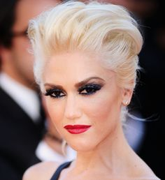 Gwen Stefani high volume platinum hair with dark eye makeup, and berry red lipstick.