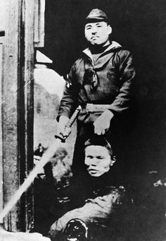 A Japanese soldier displays the severed head of a Chinese man, and a sword. 1937.