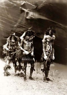 NAVAJO Yebichai, Indian War Gods. It was created in 1904 by Edward S. Curtis.    The photograph presents Three Indians: Tonenili, Tobadzischini, and Nayenezgani, in ceremonial dress, photographed against dark rock background.    We have created this collection of illustrations primarily to serve as a valuable educational tool. Contact curator@old-picture.com.    Image ID# ADCAF023