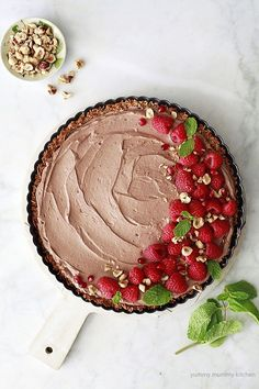 Vegan, paleo coconut chocolate mousse pie with coconut crust, raspberries, and hazelnuts. This makes a beautiful and delicious vegan Valentine's Day dessert.