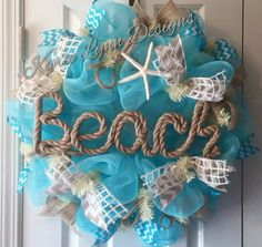 This Wreath is made out of blue deco mesh and decorated with ribbon and tubing. Accented with a Beach rope sign. Great Decor for any door!