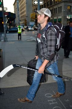Taylor Kitsch - I find it adorable that he's carrying a hockey stick, wearing cowboy boots, a plaid shirt & a baseball cap. One word. Gentleman.