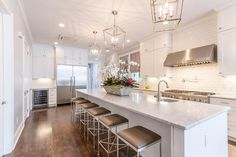 Stunning kitchen features an extra long center island topped with marble fitted with a curved prep ...