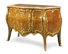 A FRENCH GILT-BRONZE-MOUNTED KINGWOOD AND BOIS DE BOUT MARQUETRY COMMODE IN LOUIS XV STYLE of bombé serpentine form, with a moulded mottled peach marble top above two long drawers on cabriole legs terminating in gilt-bronze scrolled feet, the whole mounted with foliate and scrolled reserves and inlaid with floral marquetry