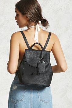A faux leather backpack featuring a pebbled texture, drawstring cinch, flap top closure with magnetic snaps, interior zipper and slip pockets, three exterior slip pockets, dual shoulder straps, and a name card tag.