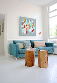 Living Room decor ideas - Simple, modern, scandinavian inspired. Bright aqua modern sofa, wood log tables, colorful art.