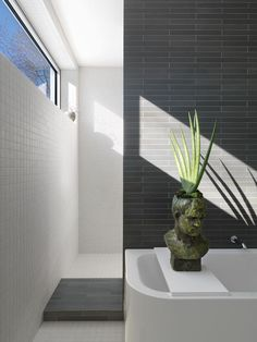 Ann Sacks and American Olean porcelain tile cover every square inch of the master bathroom. Narrow, unevenly spaced rectangular windows are a calling card of the addition and Ronan's most assertive move. Here the window is a horizontal clerestory, but others are low and vertical.