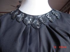 """This is such a great vintage find.  It does not have a tag with the fabric content, but is like a lightweight silky fabric.  It has a beautiful black sequin embellishment around the neckline that is 2 1/2"""" wide and has a very simple tie around the waist.  Small slit up the back with an open back and tie at the back of the neck.  It has a dolman sleeve wtih a tiny covered button closure.  There is only one belt loop, which is on the left side.  The designer tag reads """"Noel Sophisticates New…"""