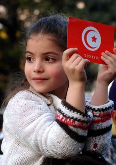 A young girl holds up a sign of the national Tunisian flag during a rally in Tunis.