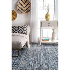 Balance breezy appeal and boho-chic flair in any ensemble with this eye-catching area rug, the perfect piece for your well-appointed and chic aesthetic. Featuring a braided cotton and jute design in blue tones, this bold piece brings textural appeal and bazaar-worthy sophistication to your look. Set it on a hardwood floor in the living room to anchor a seating group of white-finished wood tables and clean-lined linen slipper chairs, then add in hardcover art books and abstract ceramic…
