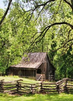 A weathered barn amongst the trees... love the split rail fence.