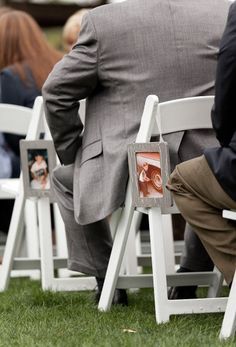 love the hanging photographs of the bride & groom as children on the chairs at the ceremony.