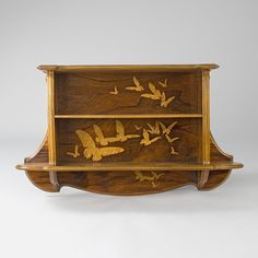 """A French Art Nouveau bookcase by Emile Gallé, featuring inlaid fruitwood marquetry, depicting flying butterflies on three interior panels. A similar piece is pictured in: Gallé Furniture, by Alastair Duncan and Georges de Bartha, Woodbridge, Suffolk: Antique Collectors' Club, 2012, p. 254, plate 1. Artist: Galle Signed: """"Gallé"""" Circa: 1905"""