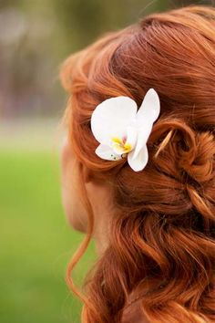 Half up wedding hairstyle with white orchid- white flowers are used to mark new beginnings