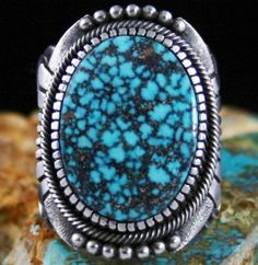 Thomas Jim Rare Gem Grade Kingman Spiderweb Turquoise Ring #ThomasJim A gorgeous and collectible red spiderweb Kingman turquoise was chosen for this fine ring. The natural gem is deep blue with electric red and chocolate complex spiderweb matrix. It is set in a high hand chiseled bezel signature to the work of Navajo jeweler Thomas Jim. Sterling silver droplets sit at each end of the ring face combined with elegant texture. Beautiful flares of silverwork are displayed above the deeply…
