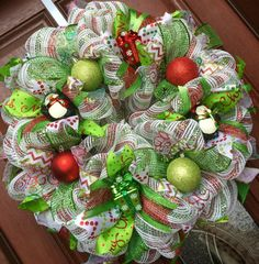 Christmas wreath in red green and white deco mesh featuring penguins and Christmas gifts.