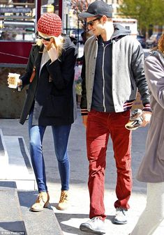Andrew Garfield colour co-ordinates with girlfriend Emma Stone's coral beanie as he slips on hipster jeans