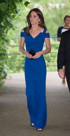 Catherine, Duchess of Cambridge showcased her figure in a dazzling cut-out shoulder dress in royal blue with a cinched-in waist, from the designer's Resort 2016 collection and features overlaid panels and an angled neckline.  She completed her look with a miniature clutch, a pair of vertiginous Gianvito Rossi heels, and what appeared to also be a pair of Cartier Diamond Tricolour Gold Trinity Hoop earrings.