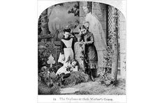 """Victorian photography showing young children around their mother's grave. Also pictured is the mother's """"spirit"""" (a model shot in trick photography.)"""